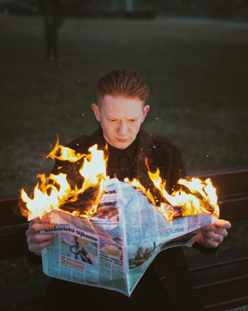 A man reading a newspaper on fire